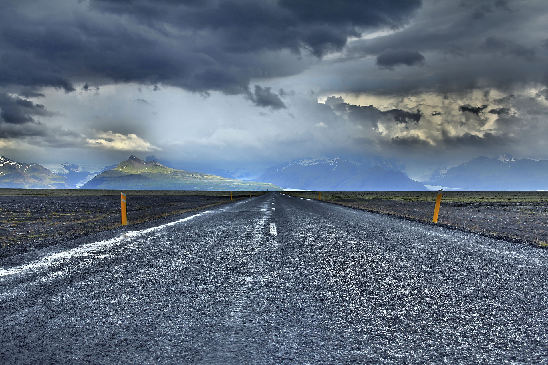 photo of road with clouds overhead